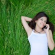 Stock Photo: Asian girl on phone lying on a meadow