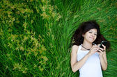 Asian cute girl texting on meadow — Stock Photo