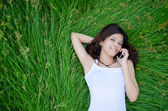Asian girl on phone lying on a meadow — Stock Photo