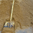Yellow shovel on sand - Stock Photo