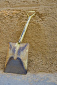 Yellow shovel on sand — Stock Photo
