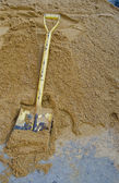 Yellow shovel on sand — Stockfoto