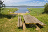 Wooden table with benches on the shore of lake — Foto Stock