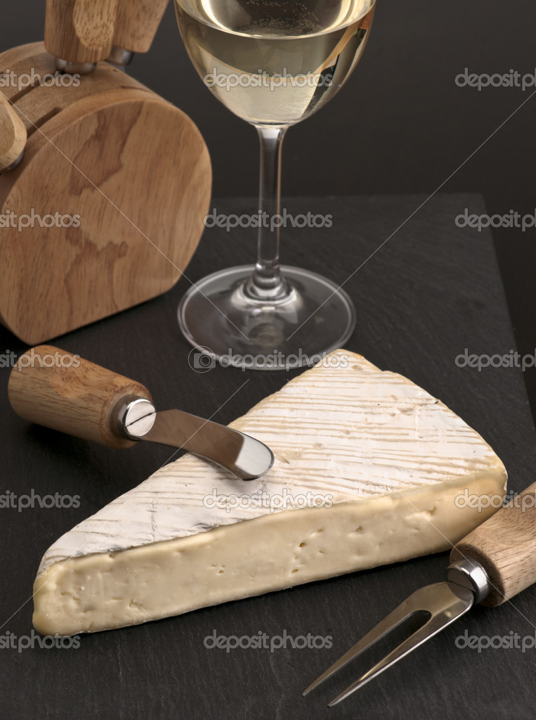 Portion of brie cheese with white wine, dark stone on base — Stock Photo #9777079