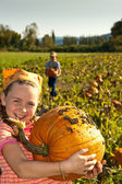Young girl with large pumpkin, in field — Stock Photo