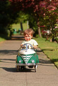 Boy driving pedal car — Stock Photo