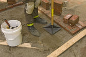Worker tamping sand for brick laying — Stock Photo