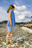 Young girl on rocky beach — Stock Photo