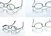 Reading glasses, spectacles and its reflection against light background — Stock Photo