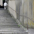 An old anonymous man ascending the stairs in an old swiss town - Stockfoto