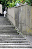 An old anonymous man ascending the stairs in an old swiss town — Стоковое фото