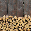 Lovely background image featuring firewood against an olden wooden wall - Stock Photo