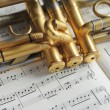 Beautiful golden trumpet on sheet music — Stock Photo
