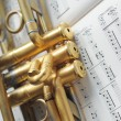 Beautiful golden trumpet on sheet music — Stock Photo #9959707