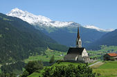 Picturesque landscape featuring a a church in the swiss alps — Stock Photo