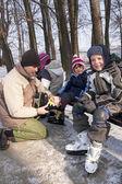 Far hjälpa barn att bära skridskor — Stockfoto
