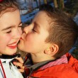 Stock Photo: Boy kissing a girl, hearts around