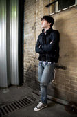 Young man leaning against wall — Stock Photo