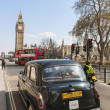 LONDON, UK - APRIL 02: Famous black cab driving by Houses of Par — Stock Photo