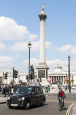 LONDON, UK - APRIL 02: Famous black cab driving by Trafalgar Squ — Stock Photo