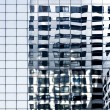 Reflections in a blue glass skyscraper — Stock Photo