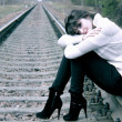A woman sits on the railroad — Stock Photo
