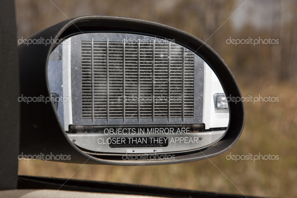 Looking through the rear view mirror you see the front grill of a large truck, obviously too close for comfort. — Lizenzfreies Foto #10084125