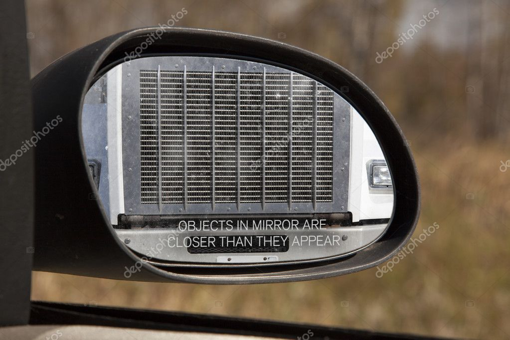Looking through the rear view mirror you see the front grill of a large truck, obviously too close for comfort.  Foto Stock #10084125