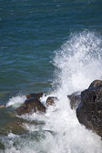 Wave breaking on rocks — Stock Photo