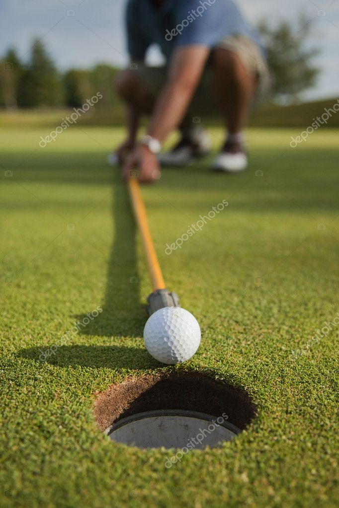 A golfer uses the flag pole to push his ball into the hole. — Stock Photo #10146304