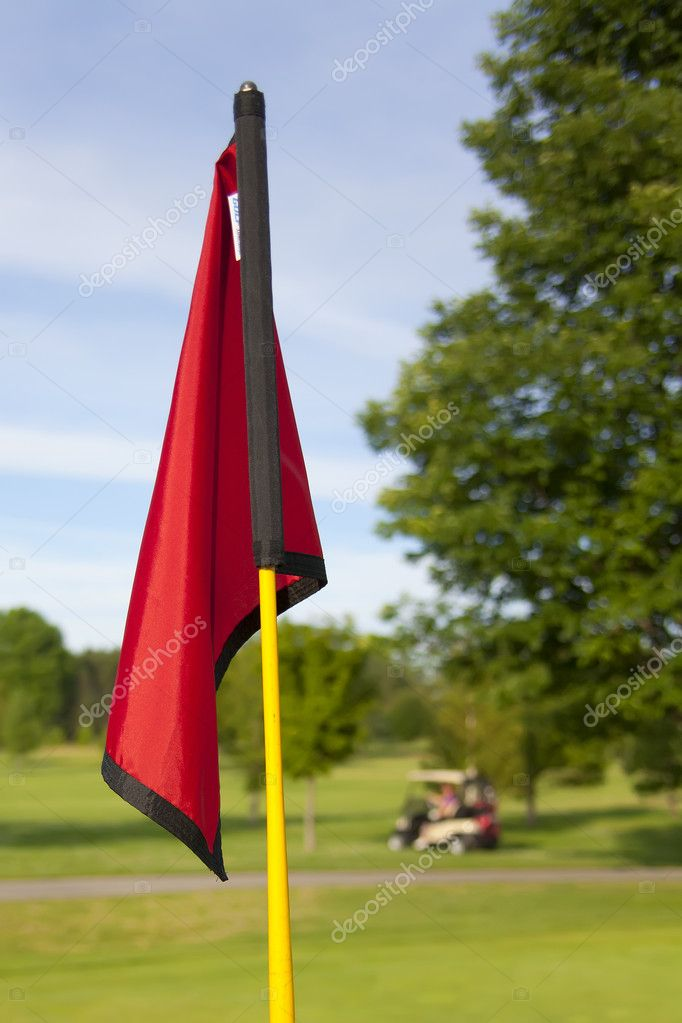 A close up shot of a red golf flag with a golf cart in the background out of focus. — Stock Photo #10146385