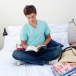 Teenager reading a book in his bedroom — Stock Photo #10277796