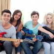 Group of teenagers playing guitar at home — ストック写真
