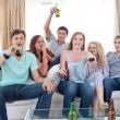 Friends drinking beer at home and watching tv — Stock Photo