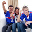 Adolescents watching a football match at home - Stock Photo