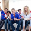 Stock Photo: Teenagers watching a football match in the living-room