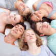 Teens sleeping on floor with heads together — Stock Photo