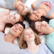 Teens sleeping on floor with heads together — Stockfoto