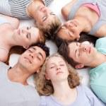 Teens sleeping on floor with heads together — Stock Photo