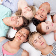 Teens sleeping on floor with heads together — Stock fotografie