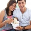Smiling couple of teenagers eating pasta — Stock Photo