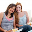 Young girls eating burgers and fries - Stock Photo