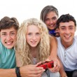 图库照片: Excited teenagers playing video games in the living-room