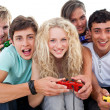 Stock Photo: Portrait of teenagers playing video games in living-room