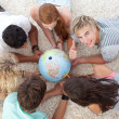 Group of teenagers on the floor examining a terrestrial world an — Stock Photo