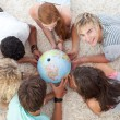 Group of teenagers on the floor examining a terrestrial world — Stock Photo