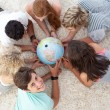 Group of teenagers on the floor examining a terrestrial world — Stockfoto #10278334