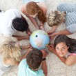 Group of friends on the floor examining a terrestrial world — Stock Photo