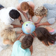 Group of teenagers on the floor examining a terrestrial world — Stock Photo #10278344