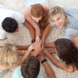 Foto Stock: Teenagers lying on the floor with hands together